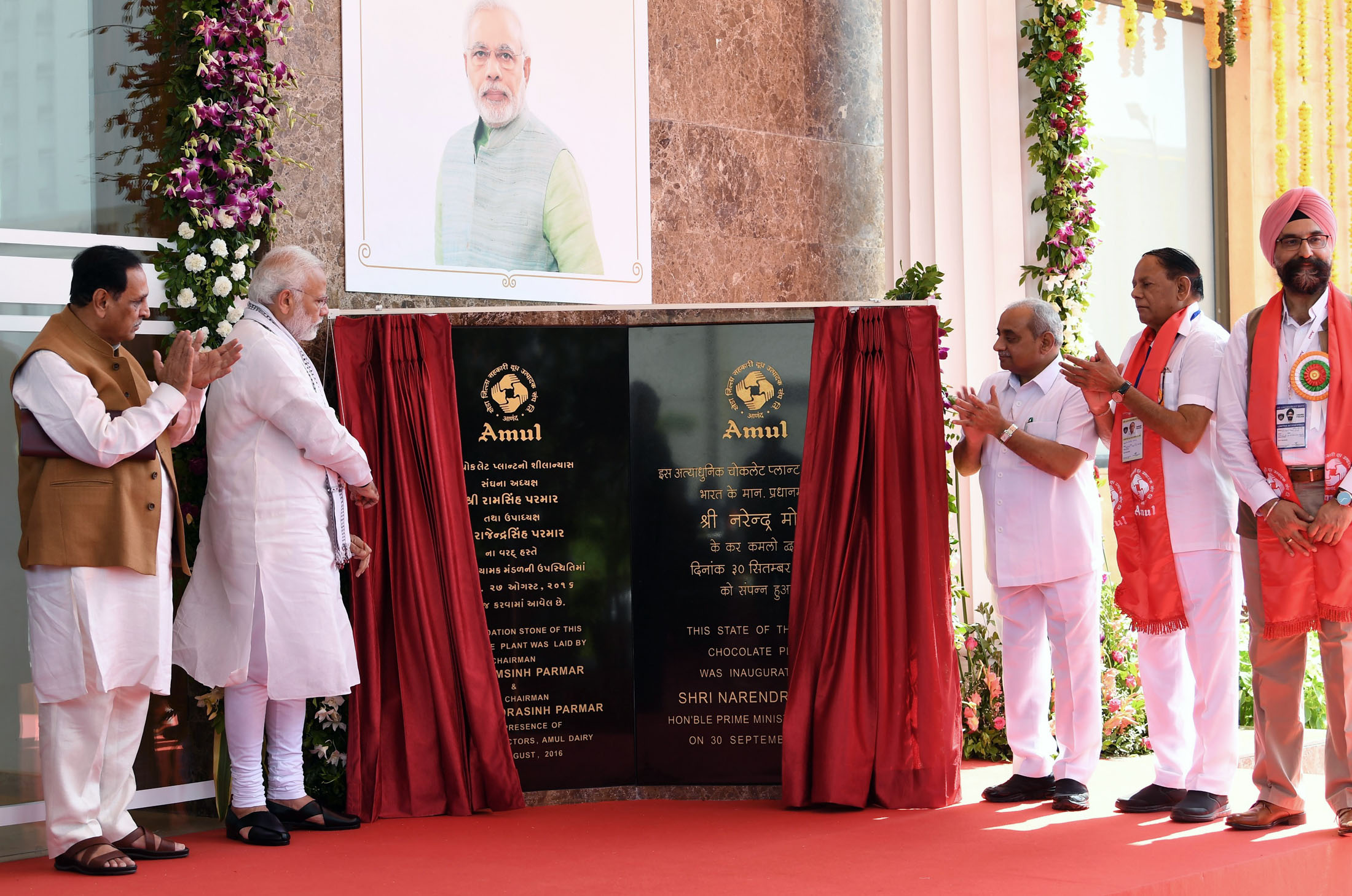 The Prime Minister, Narendra Modi inaugurating the Amul's ultra-modern Chocolate Plant, at Anand, Gujarat on September 30, 2018. The Chief Minister of Gujarat, Vijay Rupani, the Minister of State for Tribal Affairs, Jaswantsinh Sumanbhai Bhabhor and other dignitaries are also seen.